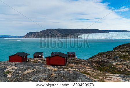 Greenland glacier nature landscape with famous Eqi glacier and lodge cabins. Tourist destination Eqi glacier in West Greenland AKA Ilulissat and Jakobshavn Glacier. Heavlly affected by Climate Change.