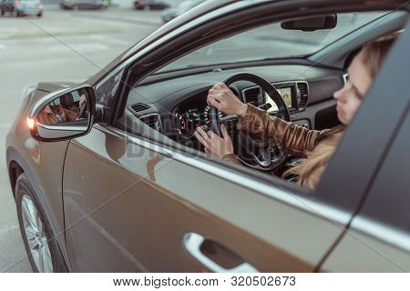 A Girl Driving A Car, Looks In A Side View Mirror, Parking At A Shopping Center, Turning At An Inter