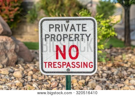 Private Property No Trespassing Sign With Rocky Terrain And Trees Background