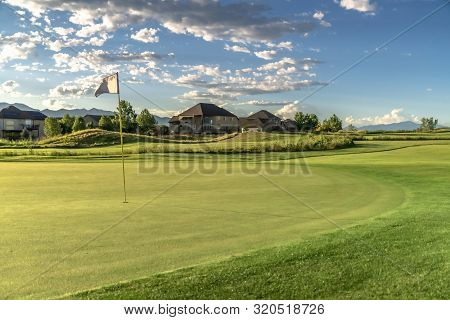 Flagstick on the fairway of a golf course with houses in the background poster