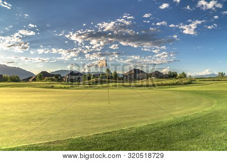 Golf course with a flagstick in the middle of the fairway under cloudy blue sky poster