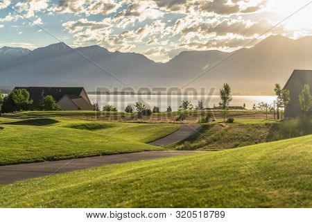Pathways and fairway on a golf course with view of lake and mountain at sunrise poster