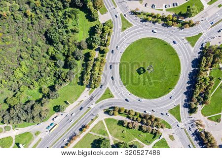 Road Roundabout With Car Lots. Aerial Photo Of A Roundabout With Grass In The Middle