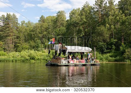 People Relax On Primitive Raft During A Canoe Rafting On The Belaya River. Tourists Rafting Down Or