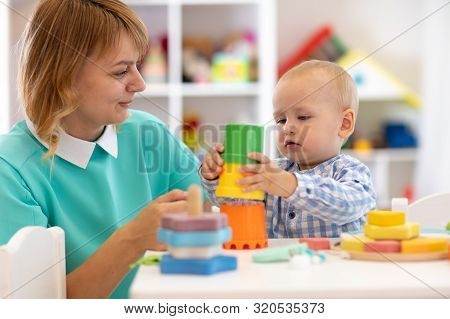 Baby With Mother In Nursery At Home. Child With Teacher Playing With Educational Cup Toys In Daycare