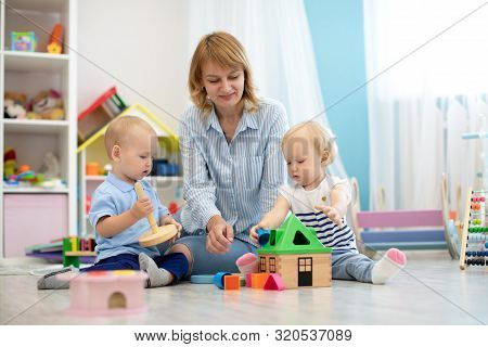Children With Teacher Playing With Educational Toys In Kindergarten. Babies With Carer In Creche Or