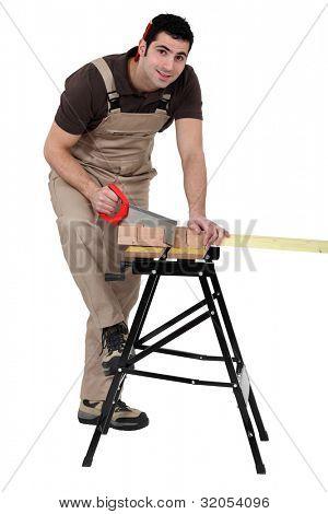 Man using miter to saw wood