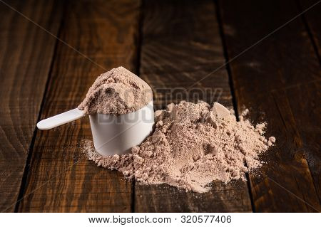 Measuring Scoop Of Whey Protein On Wooden Table To Prepare A Milkshake. Concept Of Diet, Health And