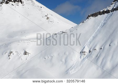Snowy Off-piste Slope With Traces Of Skis, Snowboards And Avalanches. Caucasus Mountains In Sunny Wi