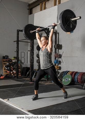 Strong female weight lifter with heavy barbell over her head.