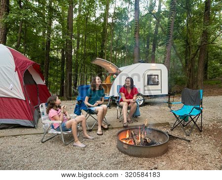 Mother and daughters camping around campfire with teardrop camper and tent in background.