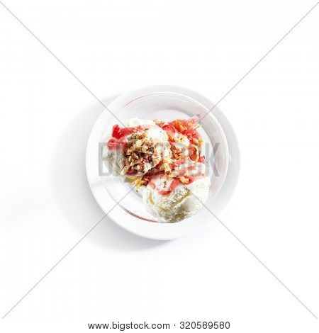 Top view of two ice cream balls or iced cream with strawberry sauce and nuts on white restaurant plate isolated. Frozen creamy yogurt ball with fruit syrup and walnuts topping topview
