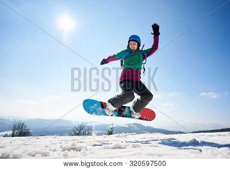 Young Female Snowboarder Jumping In Air On Copy Space Background Of Clear Bright Blue Sky And Snowy