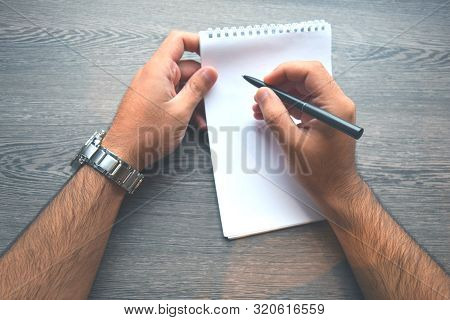 Man Writing In A Notebook.top View Of Right Handed Man With Metal Silver Watches And Writing In Note
