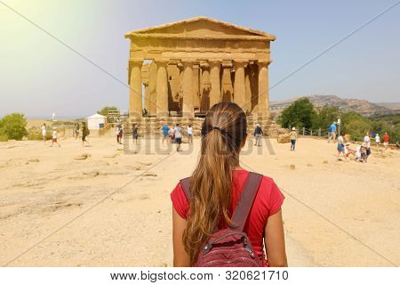 Young Woman Looks At Concordia Temple In The Valley Of The Temples Of Agrigento, Sicily. Traveler Gi