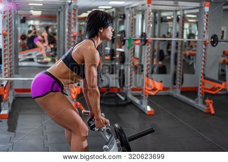 Exercising. Thrust T-shaped On The Back Muscles In The Slope. Eautiful Woman In Seductive Shorts Is