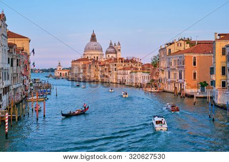 VENICE, ITLAY - JULY 19, 2019: View of Venice Grand Canal with boats and Santa Maria della Salute church on sunset from Ponte dell'Accademia bridge. Venice, Italy