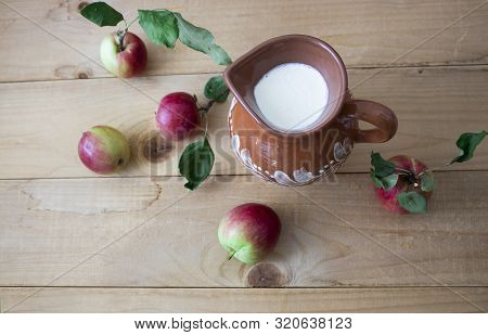 Tasty Fresh Milk Is One Of The Main Sources Of Nutrition. Milk And Apples Rustic Food. On A Wooden B