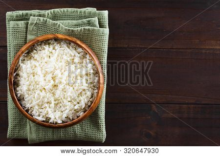 Freshly Grated Raw Cauliflower Rice In Wooden Bowl, Photographed Overhead With Copy Space On The Sid