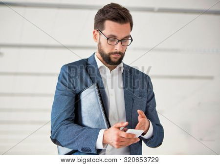 Ypung businessman with document using smartphone while standing in office