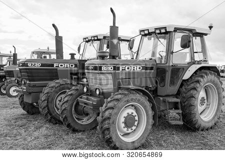 Haselbury Plucknett.somerset.united Kingdom.august 18th 2019.a Row Of Classic Ford Tractors Are Park