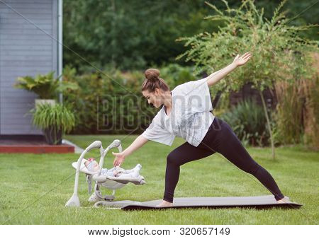Young happy smiling mother exercising fitness yoga in the garden. Healthy lifestyle and pregnancy weight loss concept.