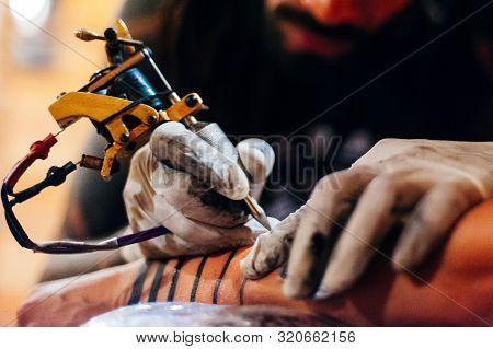 Tattoo Artist Doing Tattoo In Tatoo Salon On The Hand