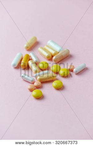 Vitamins And Supplements On Pink Paper Background. Concept For A Healthy Dietary Supplementation. Cl