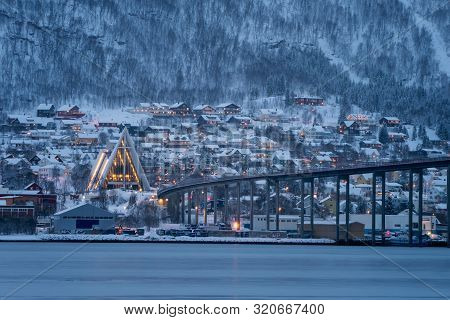 Arctic Cathedral With Famous Tromso Bridge Across Tromsoysundet Strait In The Background, Northern N
