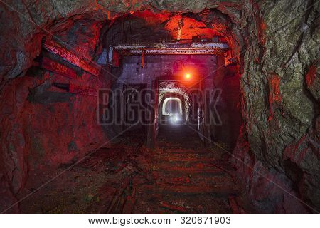 Dark dirty abandoned uranium mine with rusty remnants of railway color illuminated poster