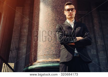 A portrait of a goodlooking young student walking in the street. Men's beauty, fashion.