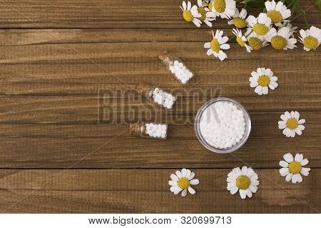 Homeopathic Globules And Glass Bottle On A Wooden Natural Background Next To Medicinal Chamomile Flo