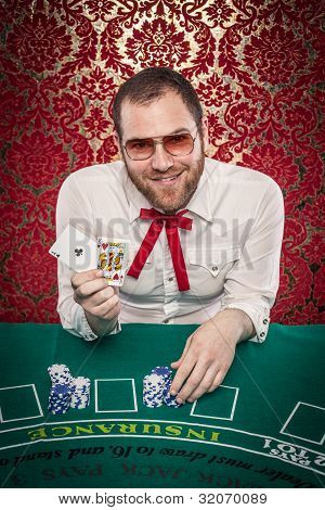 Man Playing Blackjack Holds Up Winning Hand