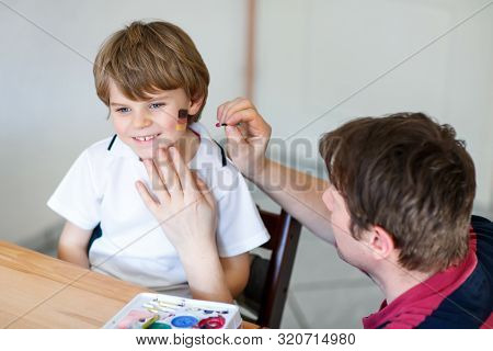 Young Dad Painting Flag On Face Of Little Son For Football Or Soccer Game. Happy Excited Preschool K