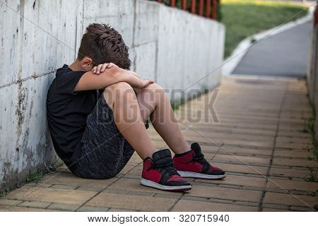 Little Boy Sad Sitting Alone At School Hides His Face. Isolation And Bullying Concept. Kid Sad And U