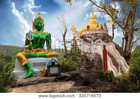 Golden Buddha statue and pagoda of the Wat Phra That In Kwaen temple, Phrae province, Thailand