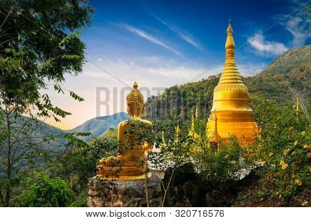 Golden Buddha statue and pagoda of the Wat Phra That In Kwaen temple with view point, Phrae province, Thailand