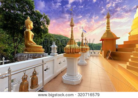 Golden Buddha statue and pagoda of the Wat Phra That In Kwaen temple , Phrae province, Thailand