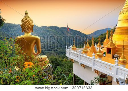 Golden Buddha statue and pagoda of the Wat Phra That In Kwaen temple at sunset with view point, Phrae province, Thailand