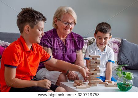 Two Boys With Grandmother Playing Game At Home, Happy Kids Playing With Senior Woman At Home. Family