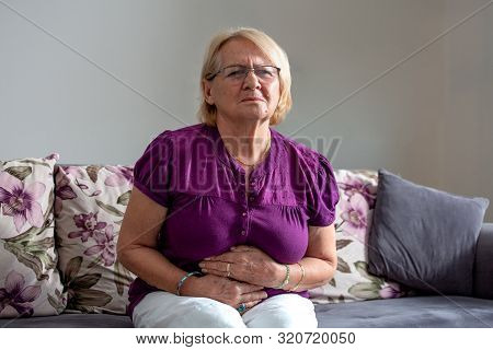 Old Age, Health Problem And People Concept - Senior Woman Suffering From Stomach Ache At Home. Senio