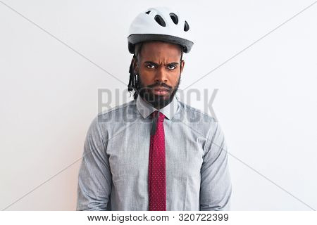 African american businessman with braids wearing bike helmet over isolated white background skeptic and nervous, disapproving expression on face with crossed arms. Negative person. poster