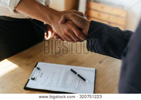 Partnership. Two Business People Shaking Hand After Business Signing Contract In Meeting Room At Com