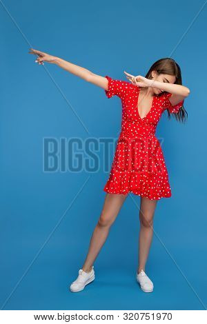 Young Woman With Bright Smile In Red Casual Dress Dubbing Over Blue Background.