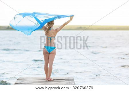 A woman holds in the wind developing scarf pareo stands near the river poster