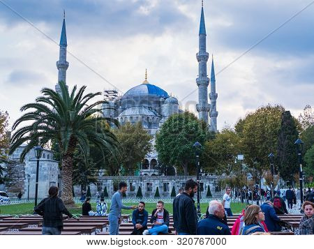 Istanbul, Turkey - October 10, 2018: People Sitting And Walking Near  Blue Mosque Or Sultanahmet Cam