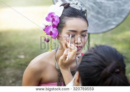 poster of Make up artist making up eye liner to Thai woman wearing thai traditional clothing