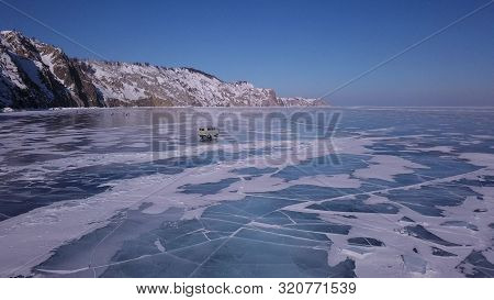 Surface of transparent fissured black ice of The Lake in winter poster