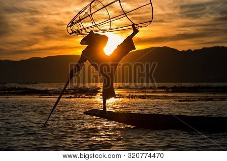 Intha Fisherman Posing With Conical Net At Sunset, Inle Lake In The Nyaungshwe Township Part Of Shan