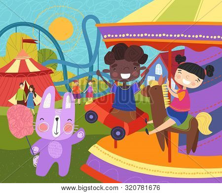 Two Young Children Having Fun At The Fairground Riding On A Colorful Carousel Or Merry-go-round Watc